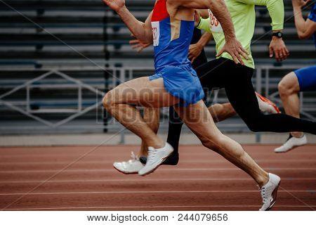 race men sprinters runners in 100 meters at track stadium poster