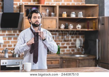 Handsome Loner Businessman Tying Necktie At Kitchen