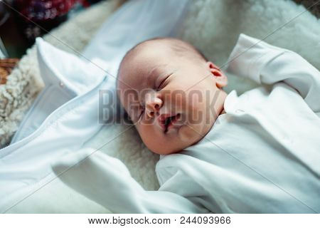 Soft Portrait Of Peaceful Sweet Newborn Infant Baby Lying On Bed While Sleeping In A Bright Room. Ma