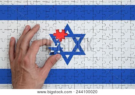 Israel Flag  Is Depicted On A Puzzle, Which The Man's Hand Completes To Fold