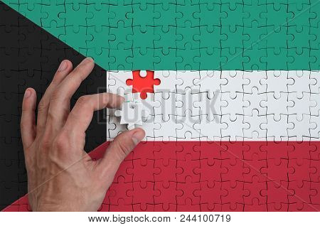 Kuwait Flag  Is Depicted On A Puzzle, Which The Man's Hand Completes To Fold