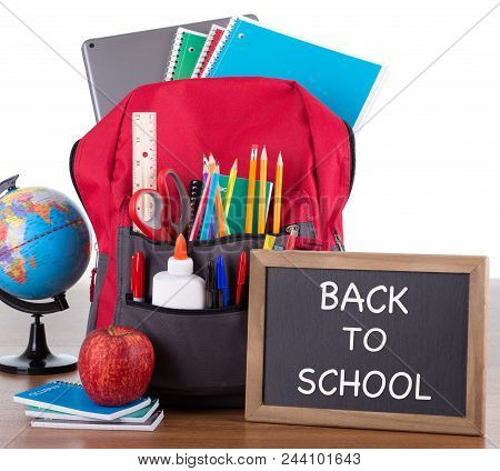 Backpack With An Assortment Of School Supplies With Back To School Written On A Chalkboard On A Wood