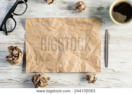 Top view of modern creative workplace with creased piece of sheet, pen, crumpled paper balls and cup of coffee placed on wooden table. Concept of finding of outstanding idea. poster