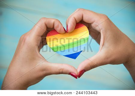 Lgbt Concept.  Womens Hands On Blue Background Holding Heart Rainbow Colors. Lgbt Day Concept