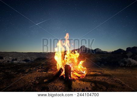 Exploring The Wilderness In Summer. A Glowing Camp Fire At Dusk Providing Comfort And Light To Appre
