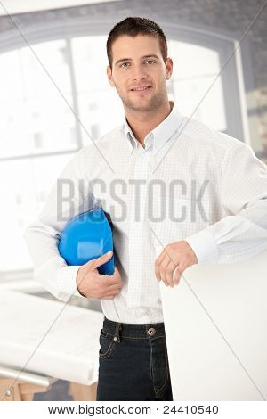 Young architect smiling in bright office.?