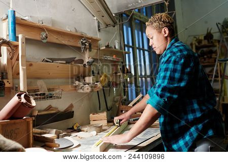 Side view of female woodworker standing near workbench and measuring lumber plank while working in workshop.  poster
