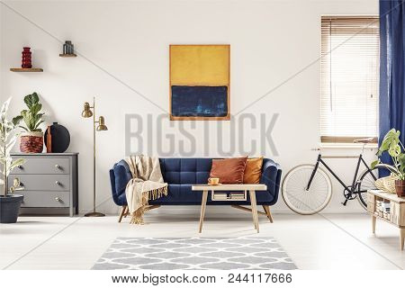 Yellow And Blue Painting Hanging On White Wall In Bright Living Room Interior With Grey Cupboard, Go