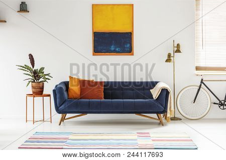 Blue And Orange Painting Hanging On A White Wall Above An Elegant Sofa With Decorative Cushions In L