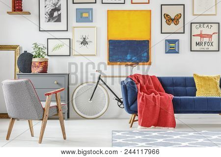 Red Blanket Thrown On Blue Settee In Bright Sitting Room Interior With Patterned Armchair, Bike And