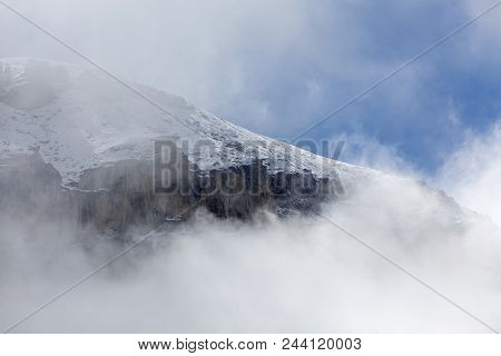 Wyoming Mountain Covered With Snow, Steep Cliff, Clouds