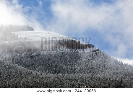 Wyoming Mountain With Light Snow On Evergreen Trees, Clouds