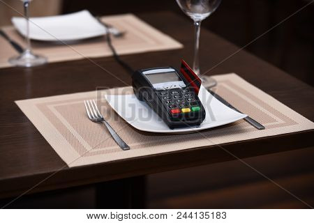 Payment With Credit Card. Credit Card Terminal Near Glasses And Plates On Table Background. Credit C