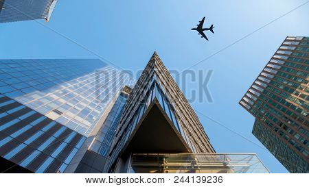 An image of a plane flying over modern buildings of New York City