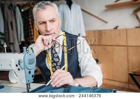 Handsome Pensive Tailor Sitting At Table With Sewing Machine At Sewing Workshop