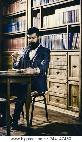 Aristocrat On Thoughtful Face Reading Book. Oldfashioned Man Holds Cup With Tea. Man In Classic Suit