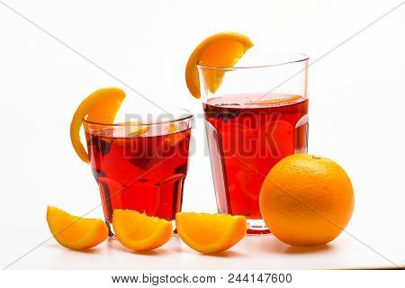 Cocktail Concept. Glasses With Orange Drink Near Juicy Orange Fruit On White Background, Close Up. D