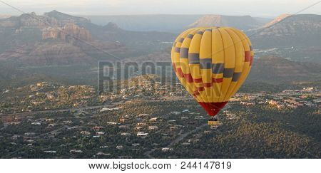 A Hot Air Balloon Soars Above The Red Rocks Of Sedona, Arizona