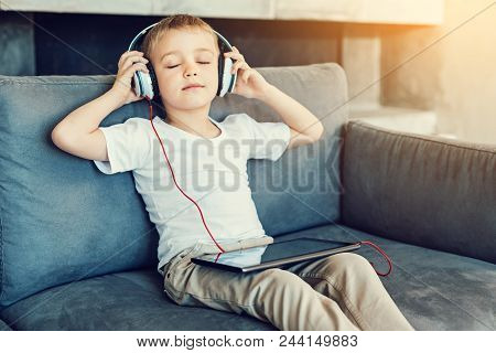 Relaxation. Pleasant little relaxed child sitting with his eyes closed while listening to the calm music poster