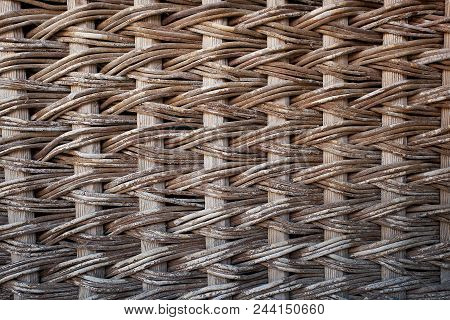 Woven from rods wooden fence. The texture of the wood and netting.