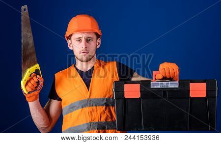 Carpenter Concept. Man In Helmet, Hard Hat Carries Toolbox And Holds Handsaw, Blue Background. Worke