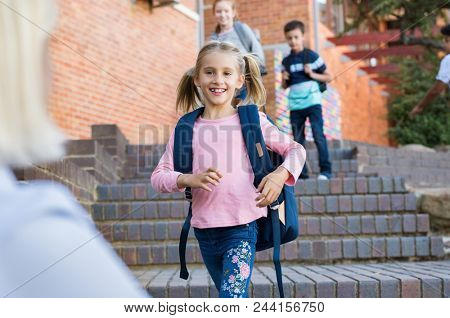 Happy cute girl running with stretched arms towards motherl. Young school child feeling happy after lesson at primary school. Elementary student kid running into mother's hands to hug her after school