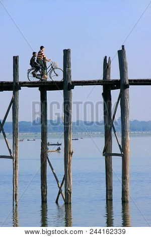 Amarapura, Myanmar - December 31: Unidentified Kids Ride Bicycle On U Bein Bridge On December31, 201