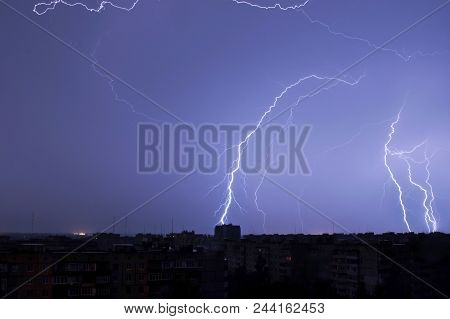 Lightning In The Night Sky Strikes The Roof Of The House.