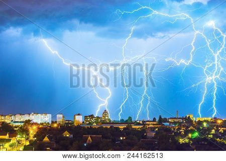 Lightning Over The City In The Night Sky Strikes The Roof Of The House.
