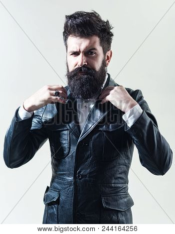 Barber Shop Concept. Fashion. Trendy Clothes. Bearded Man In Black Jacket Correct The Collar. Leathe