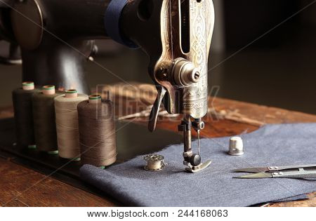 Vintage sewing machine with fabric and threads, closeup