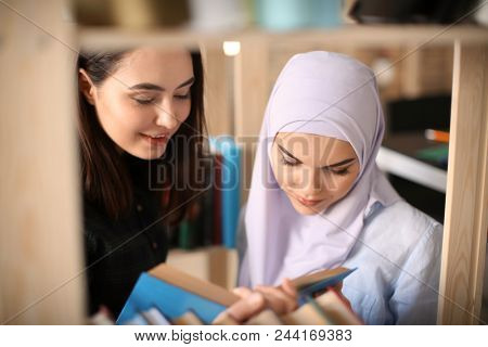 Female student and her Muslim classmate in library