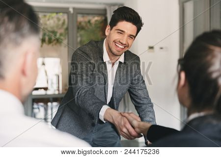 Business, career and placement concept - happy european man wearing suit rejoicing and shaking hands with group of employee when was recruited during interview in office