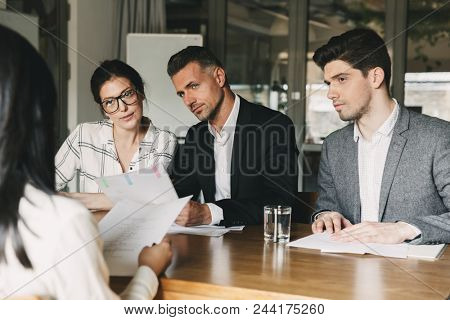 Business, career and placement concept - board of directors of international company sitting at table in office and interviewing woman for staff