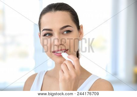 Young Woman Applying Balm On Her Lips Indoors