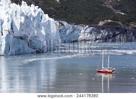 Little Boat Getting Closer To The Glacier In Glacier Bay National Park (alaska).