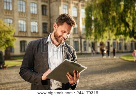 Image of successful businessman 40s holding clipboard and examining documents while standing in front of old building in park