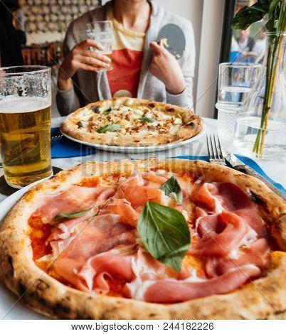 Woman And Delicious Pizza Salsiccia E Carciofi And Prosciutto
