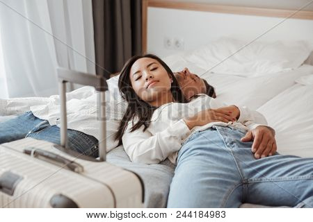 Photo of attractive couple man and woman in casual jeans clothing resting together and lying in bed at hotel room. Holiday or vacation concept