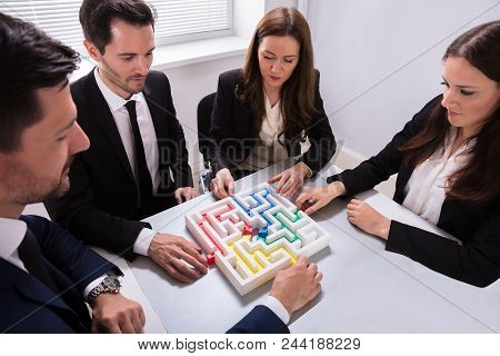 Young Businesspeople Holding Multi Colored Arrow Solving Maze On Desk At Workplace