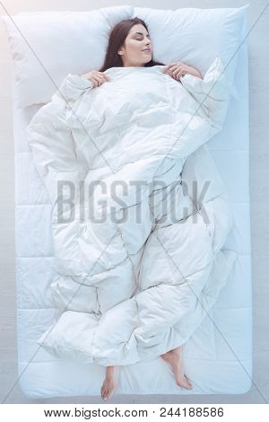 Comfortable Sleep. Top View On A Joyful Brunette Covered In A Duvet Falling Asleep In A Starfish Pos