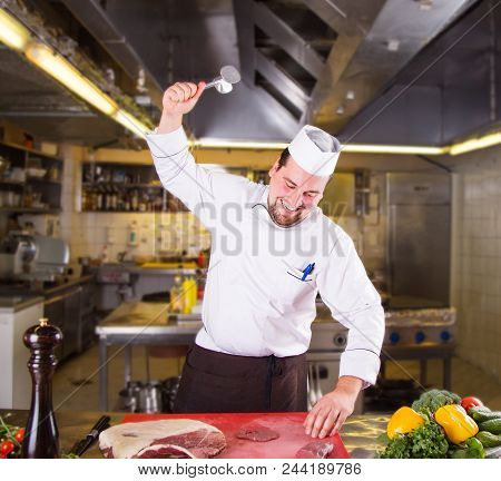 Male Chef With A Happy Face Beats A Piece Of Raw Meat At The Restorant Kitchen. Tenderizing Meat. Sm