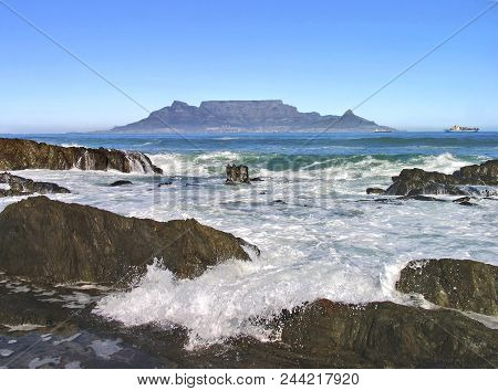 Seascape, White Waves Washing Over Some Rocks In  The Fore Ground And Table Mountain In The Back Gro