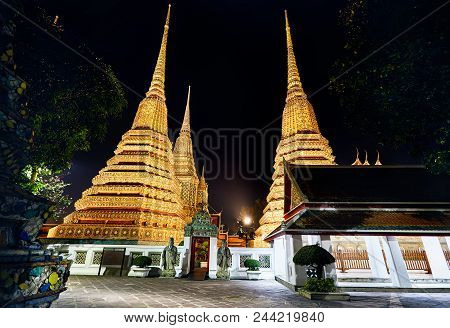 Buddhist Temple Wat Pho With Golden Chedi In Bangkok At Night Sky In Thailand. Famous Landmark And S