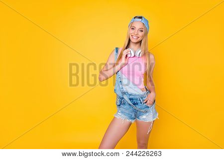 Portrait Of Pretty Charming Girl In Cap With Headset On Neck Holding Hand In Pocket Of Denim Shorts