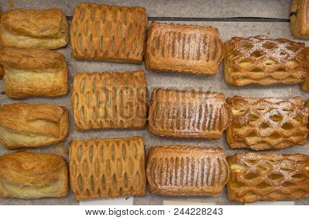 Puff Pastry Rolls. Fresh Sweet Baking On Papyrine. Several Kinds Of Crispy Pies Lie In Rows On A Bak