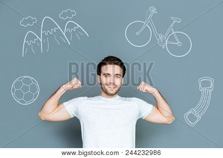 Strong Man. Young Active Man Looking Strong And Smiling While Showing His Muscles