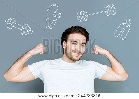 Happy Sportsman. Professional Young Sportsman Feeling Glad And Smiling While Showing His Strength