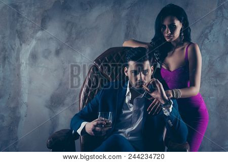 Portrait Of Brutal Gentleman In Formal Wear Sitting In Leather Chair Holding Glass With Whiskey Ciga