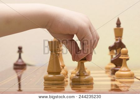 The Children's Hand Puts A Chess Figure On The Game Field